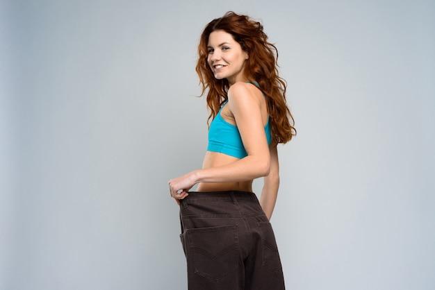 La ragazza è molto magra dopo l'allenamento nella stanza grigia.