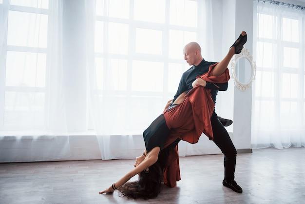 La ragazza è quasi sottosopra. giovane donna graziosa in vestiti rossi e neri che ballano con il ragazzo calvo nella stanza bianca