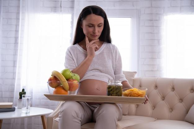 La ragazza è sceglie tra cibo sano e malsano.