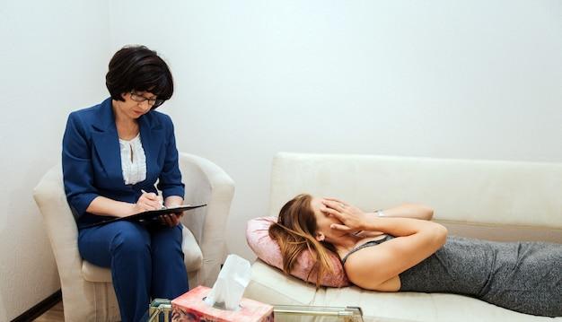 La ragazza è sdraiata sul divano e si copre il viso con le mani. lei sta piangendo. la ragazza è disperata. la terapista è seduta accanto a lei e sta scrivendo informazioni.