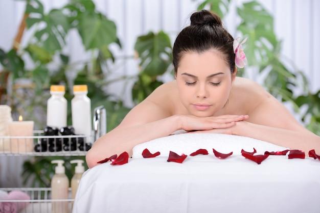La ragazza è sdraiata sul letto per il massaggio.