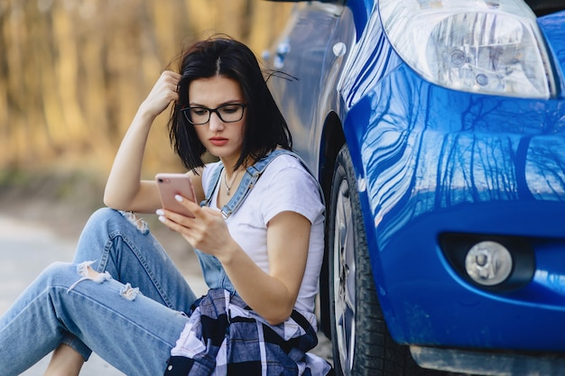 La ragazza è seduta accanto alla macchina rotta con un cappuccio aperto e parla al telefono