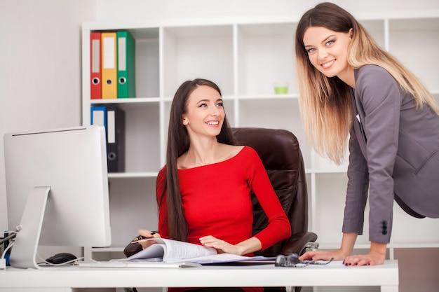 La ragazza è seduta al tavolo davanti al computer portatile e tenendo la penna, la donna è in piedi accanto a lei