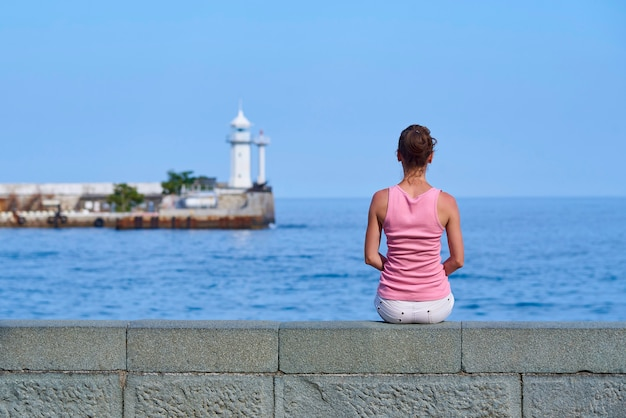 La ragazza è seduta in riva al mare e sta guardando in lontananza il faro.