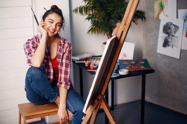La ragazza elegante disegna in uno studio di arte