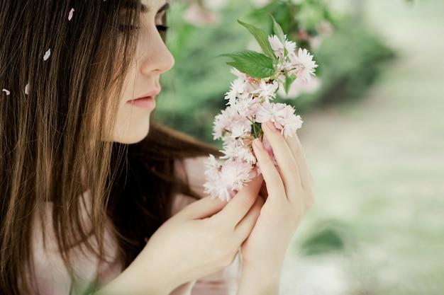 La ragazza esamina il ramo di sakura nel parco