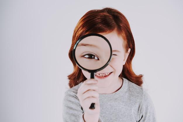 La ragazza esamina la lente d'ingrandimento, aumentando le dimensioni dell'occhio.