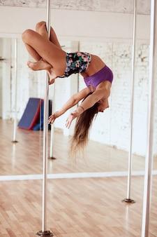 La ragazza esegue l'yoga nello studio di ballo del palo