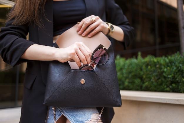 La ragazza estrae gli occhiali da una borsa. la donna alla moda mette gli occhiali nella sua borsa