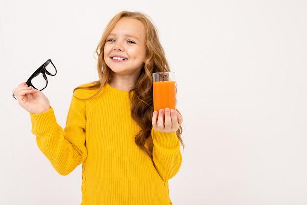 La ragazza europea sorridente si è tolta gli occhiali e tiene in mano un bicchiere di succo di carota