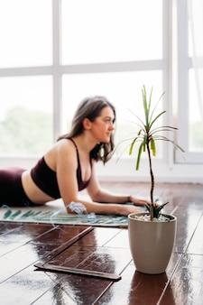 La ragazza fa esercizi, stretching, yoga, o vicino alla finestra, tuta da yoga, corpo, magrezza e salute, incenso, piante, odore