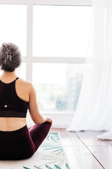 La ragazza fa esercizi, stretching, yoga, vicino alla finestra, tuta da yoga, corpo, magrezza e salute