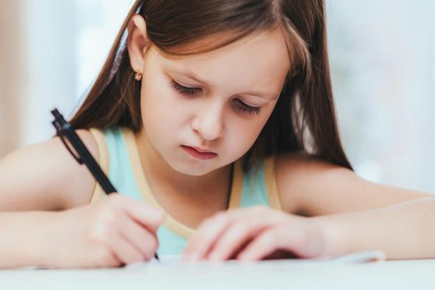 La ragazza fa la prima elementare nella stanza facendo i compiti