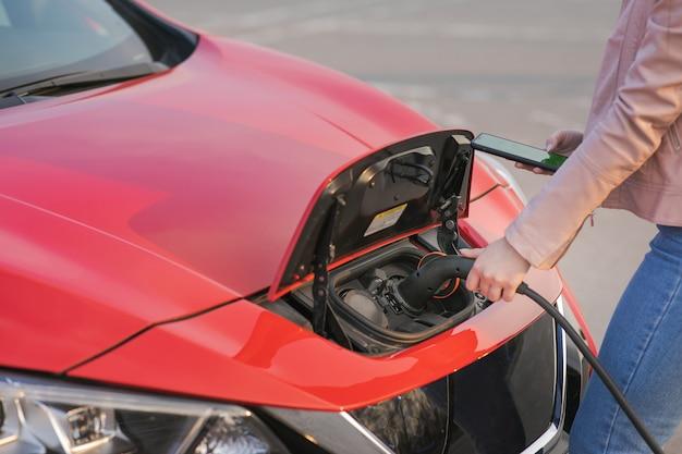 La ragazza fa pagare l'auto elettrica alla stazione. la donna sta tappando il veicolo elettrico per caricare la batteria dell'auto. auto elettrica in carica in strada.