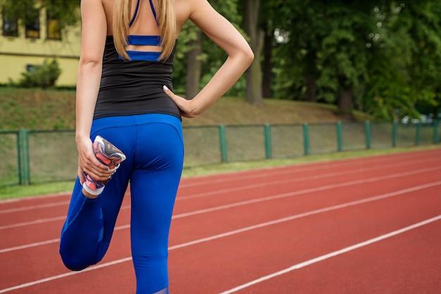La ragazza fa un riscaldamento prima di una maratona allo stadio
