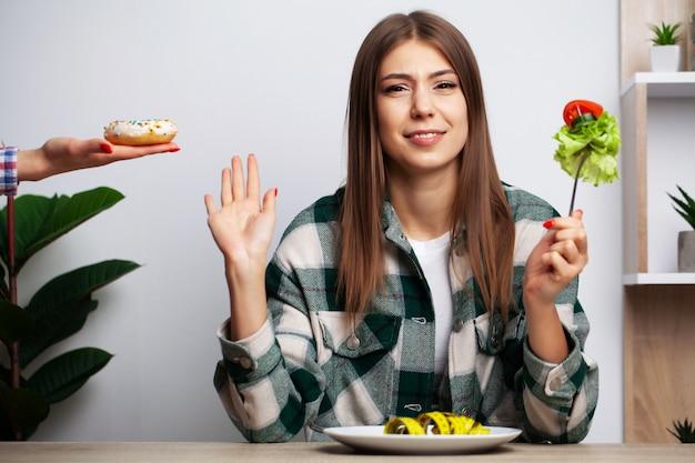 La ragazza fa una scelta tra cibo sano e dannoso