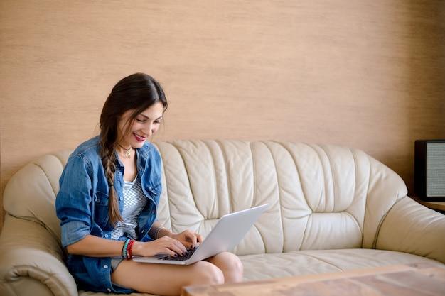 La ragazza felice acquista online sul suo computer portatile