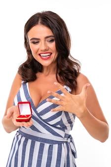 La ragazza felice con capelli castani in un vestito con una scollatura tiene una scatola con un anello di fidanzamento su un bianco