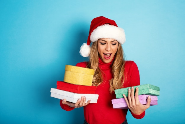 La ragazza felice con il cappello di natale riceve molti regali. sfondo ciano
