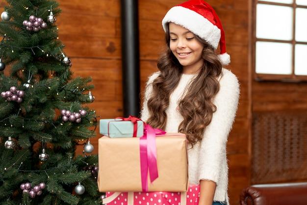 La ragazza felice del colpo medio con i regali si avvicina all'albero di natale