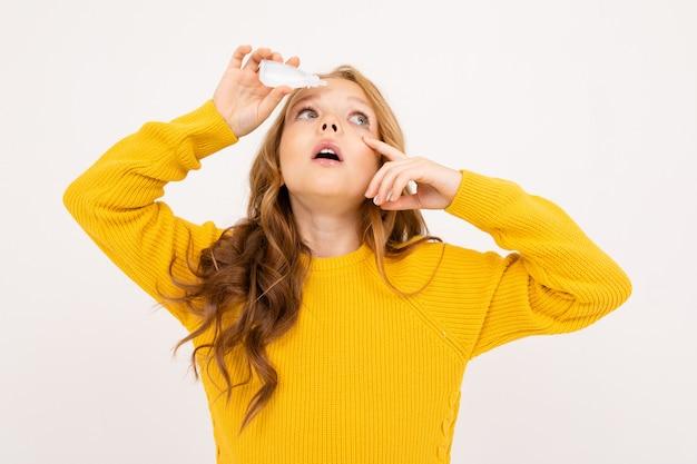 La ragazza felice dell'adolescente con capelli rossi, la maglia con cappuccio e i pantaloni gialli giudica le lenti a contatto isolate su fondo bianco