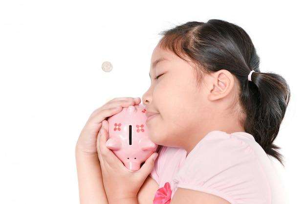 La ragazza felice dorme e abbracciando il porcellino salvadanaio rosa