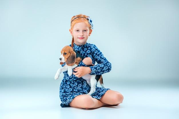 La ragazza felice e un cucciolo di beagle sulla parete grigia