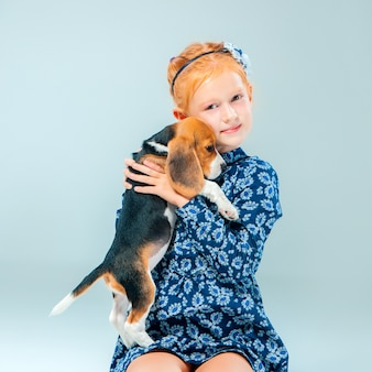 La ragazza felice e un cucciolo di beagle