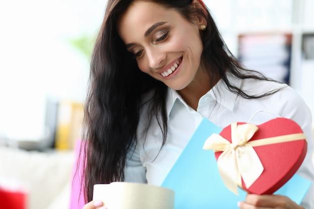 La ragazza felice esamina il cuore del modulo del regalo dal pacchetto