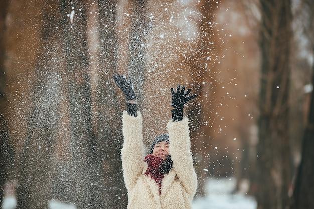 La ragazza felice gettando neve
