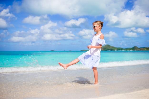 La ragazza felice gode del fondo di vacanze estive l'acqua del turchese e del cielo blu nel mare
