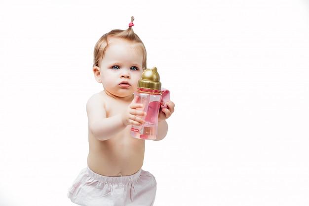 La ragazza felice in pannolino tiene la bottiglia dell'alimento e della bevanda della nutrizione della mano del latte per il quadro televisivo neonato con il piccolo bambino isolato su bianco.