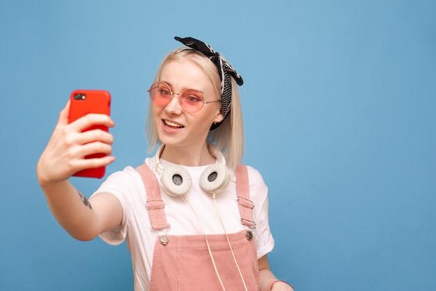La ragazza felice in vestiti luminosi e le cuffie alla moda che stanno su un fondo blu fa il selfie e sorride