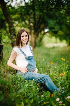 La ragazza felice incinta si tiene per mano sullo stomaco nel giardino con gli alberi.