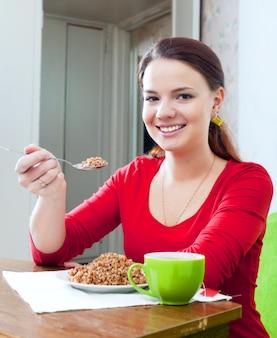 La ragazza felice nel rosso mangia il grano saraceno