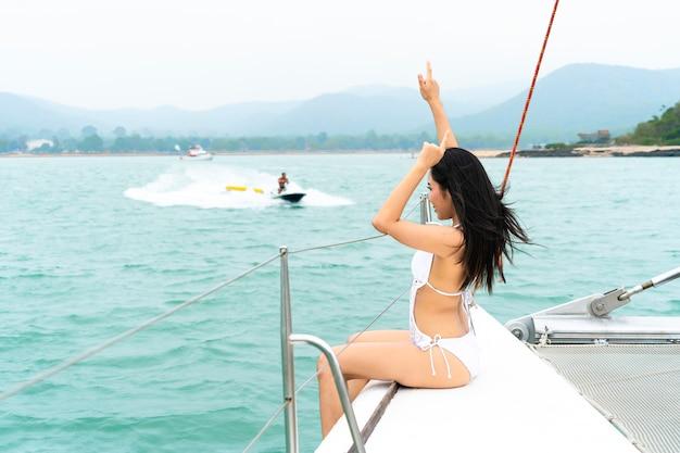 La ragazza felice sexy del bikini si siede sull'yacht della barca con davanti al mare ed al cielo