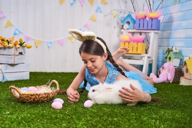 La ragazza felice si siede sull'erba con le uova dipinte e nutre il coniglio dell'animale domestico, il giorno di pasqua