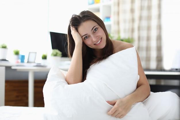 La ragazza felice si sveglia al mattino e si siede sul letto.