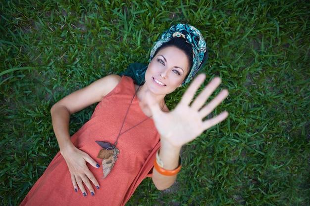 La ragazza felice si trova sull'erba e tende la sua mano
