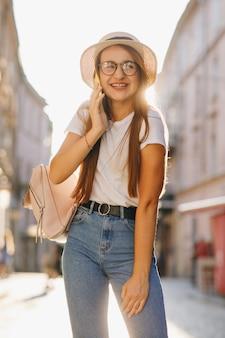 La ragazza felice sorridente cammina e chiama il suo amico, facendo uso dell'aggeggio digitale.