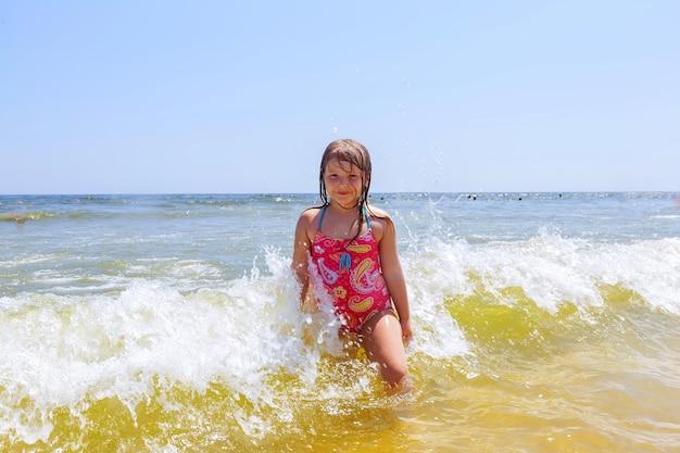 La ragazza felice su un oceano tropicale della spiaggia si diverte con spruzzata