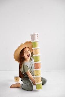 La ragazza felice tiene una torre dei vassoi di carta colorati. concetto di stoviglie usa e getta eco.