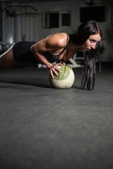 La ragazza fitness fa flessioni sulla palla