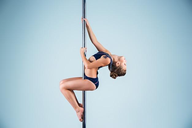 La ragazza forte e aggraziata che esegue esercizi acrobatici sul pilone