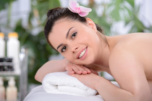 La ragazza giace su un asciugamano e sorride.