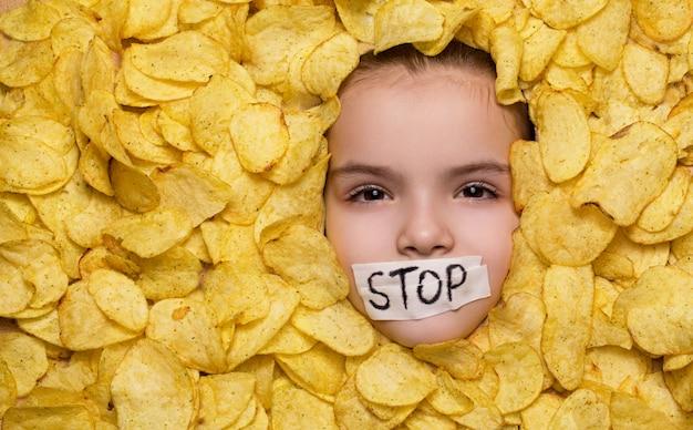 La ragazza giace tra le patatine nastrate la sua bocca con il segnale di stop