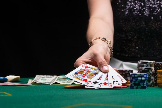 La ragazza gioca a poker in un casinò con patatine, dollari e vino