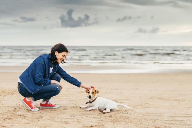 La ragazza gioca con un cane in riva al mare