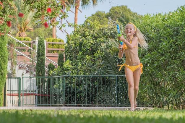 La ragazza gioca il gioco di combattimento della pistola ad acqua nel giardino, divertimento di summertie