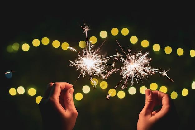 La ragazza gode di giocare con i piccoli fuochi d'artificio a mano dello sparkler